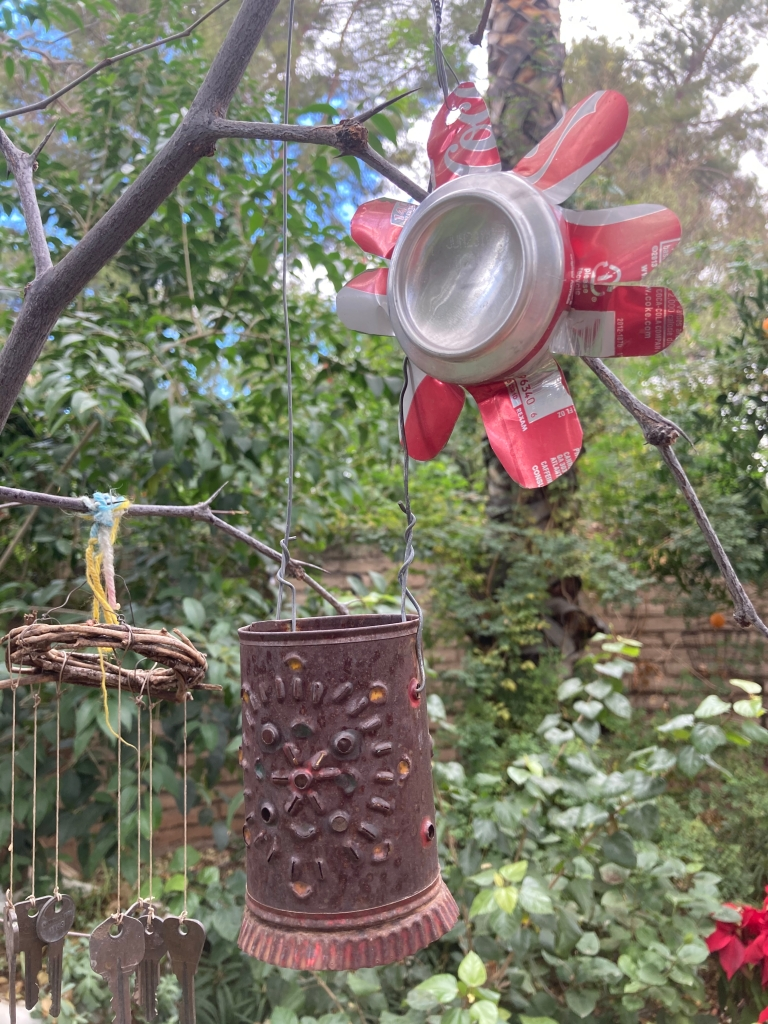 Picture of a flower made from a Coke can, along with a bird feeder made from a rusty can and wind chimes made with keys.